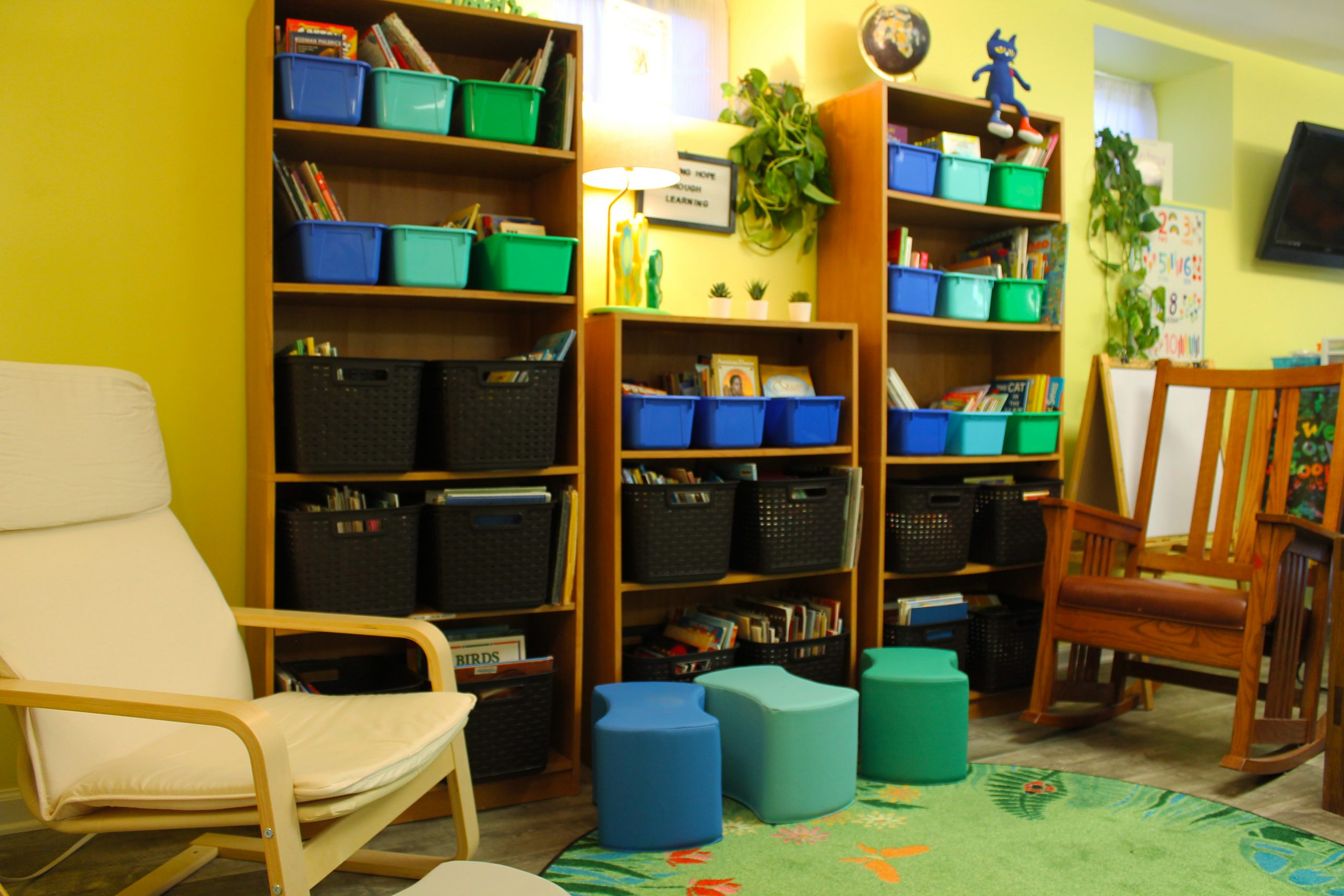Reading area. Bookshelves against the wall. Stools and a comfortable reading chair next to an open area rug. Perfect for story time or independent reading.