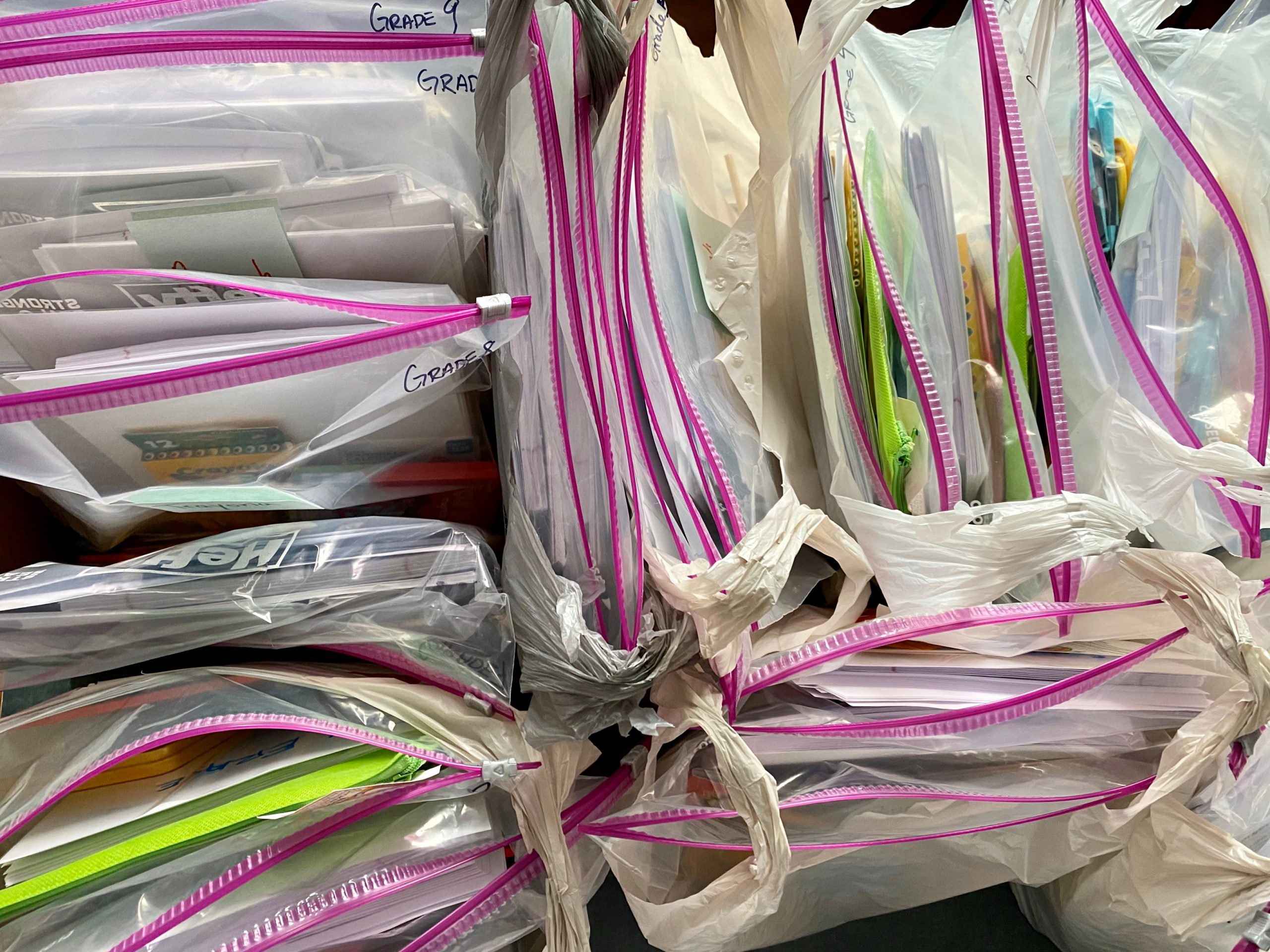 Learning supplies packaged in gallon bags, labeled by grade. Ready for delivery.